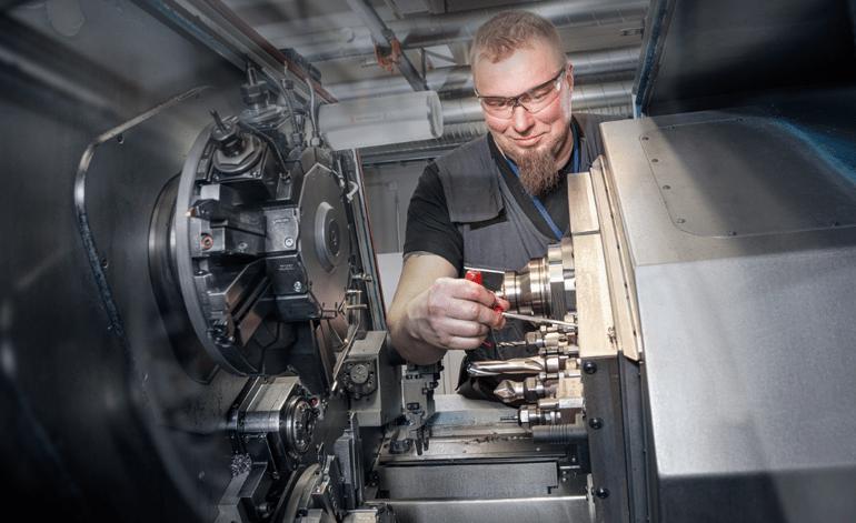 Myllyn Koneistuksen Jani Toivanen asettamassa CNC-sorvia.