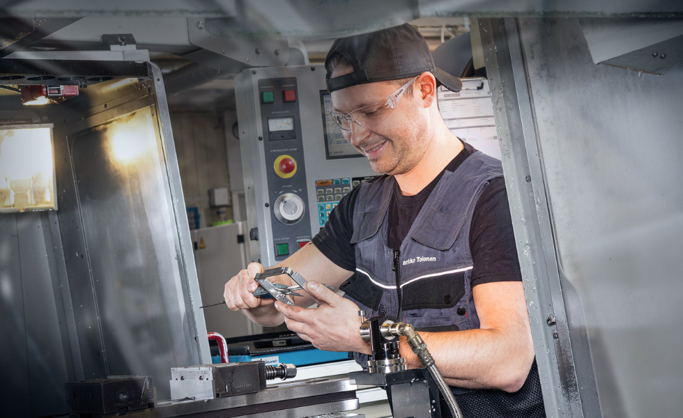 Jarkko Tolonen CNC-jyrsimellä tarkistusmittaamassa koneistettua kappaletta. Kuvaaja: Harri Mäenpää, Studio Korento